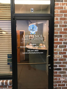 Close up photo of glass door entrance to Lawrence Family Dentistry office, red brick building, logo on door