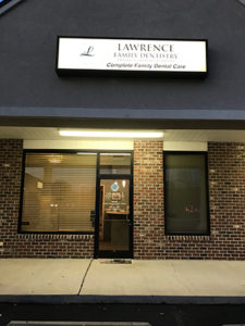 Front of dental office, red brick building, office sign that says Lawrence Family Dentistry Complete Family Dental Careon roof
